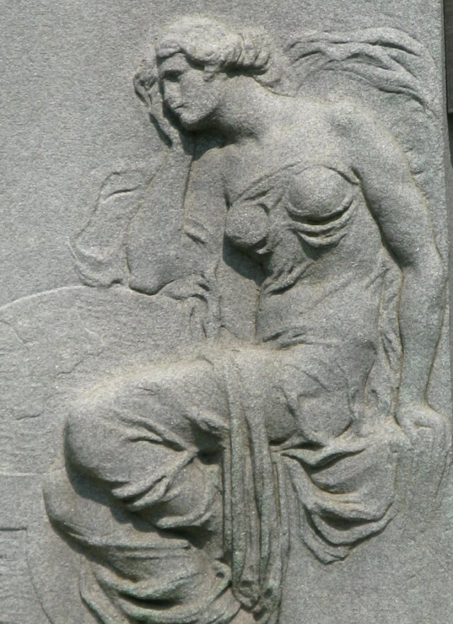 This is a detail carved into the side of a pillar that holds a bronze bust of some old white dude.